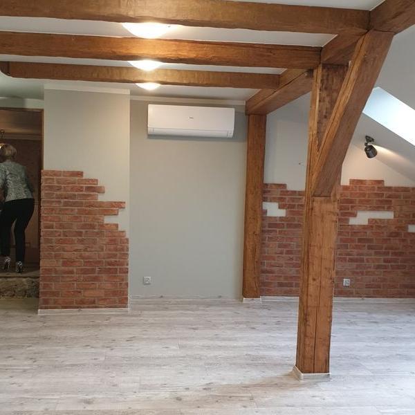 biały klimatyzator wewnątrz zdobionego drewnem pokoju